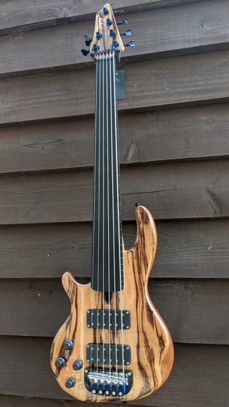 Left handed 6-string Mk3 with zebrano facings, matching head veneer, clear gloss body, a fretless ebony fingerboard with edge lines and black tuners & retainer.